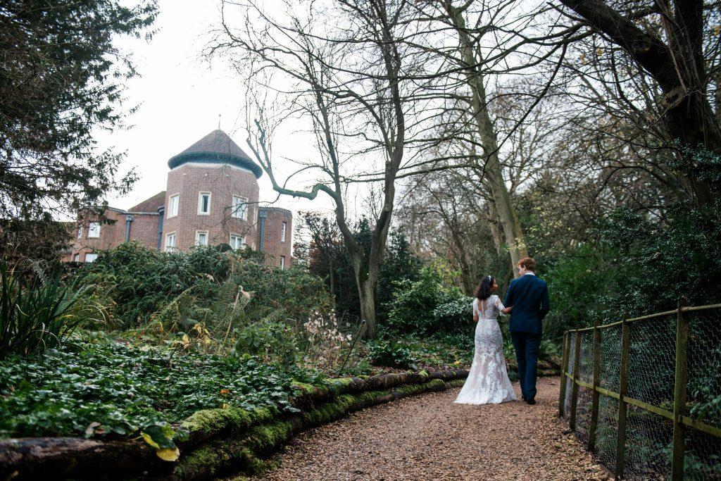 Wedding couple walk garden path with arms linked in. Cambridge wedding