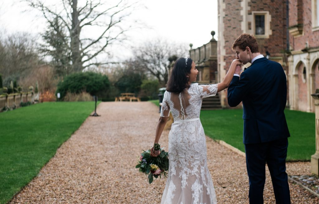 Groom tenderly kisses his brides hand with Madingley Hall in the background at COVID friendly wedding