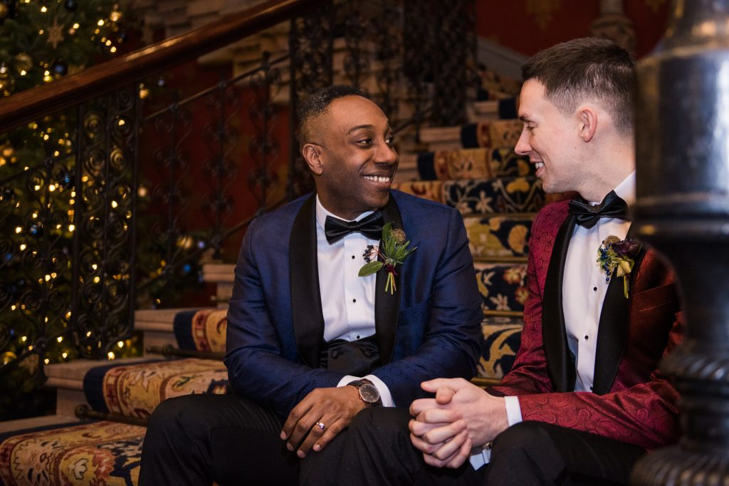 Wedding couple smiling at each other on grand staircase of renaissance hotel