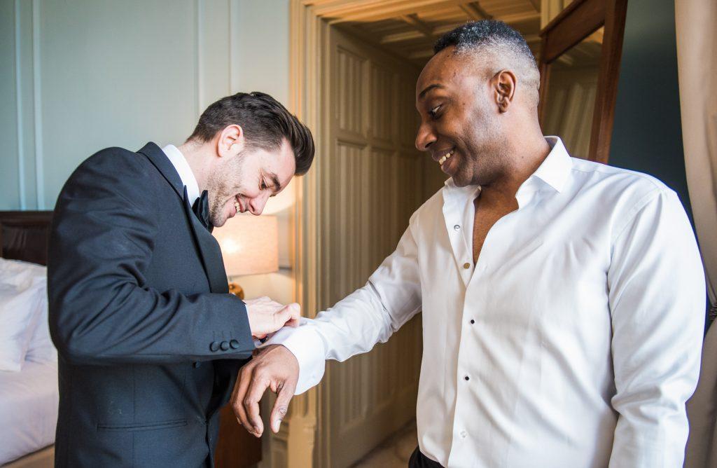 best man helps groom secure his cufflinks