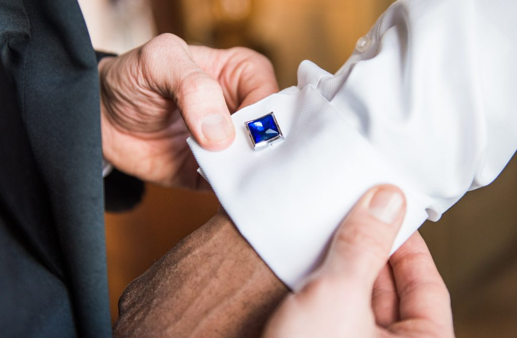 Close up of blue cufflinks on grooms sleeve. candid photographer