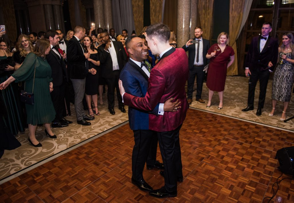 grooms holding each other close for the first dance. documentary wedding photography