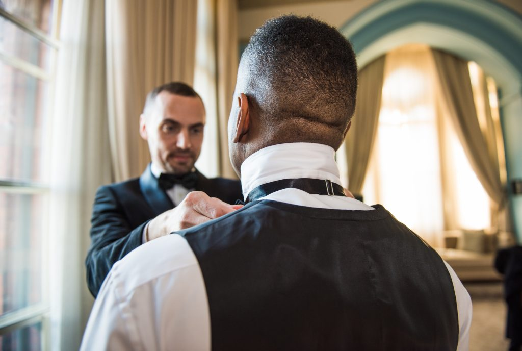 Picture of best man helps groom put on his bow tie captured candidly by wedding photographer