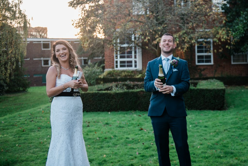 wedding couple opening champagne during reception of their covid micro wedding
