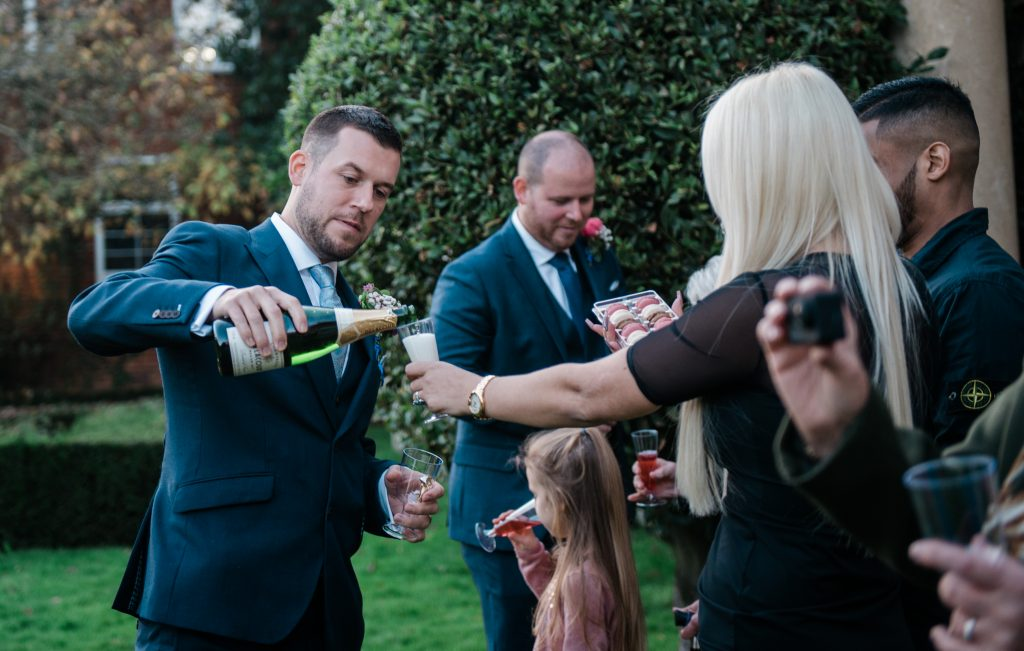 groom pouring champagne during reception of his covid micro wedding