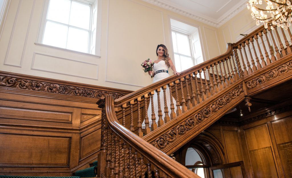 beautiful bride walking down the stairs in wedding dress at her covid micro wedding