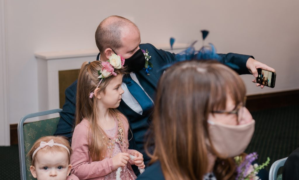 family taking a selfie wearing masks at covid micro wedding