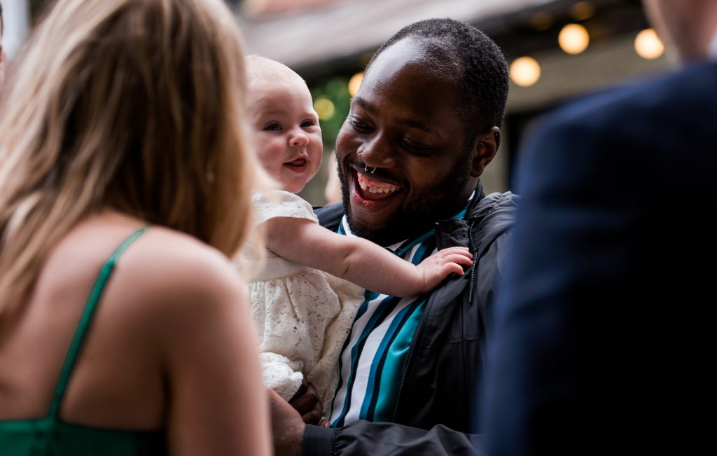 smiling wedding guest holding a laughing baby