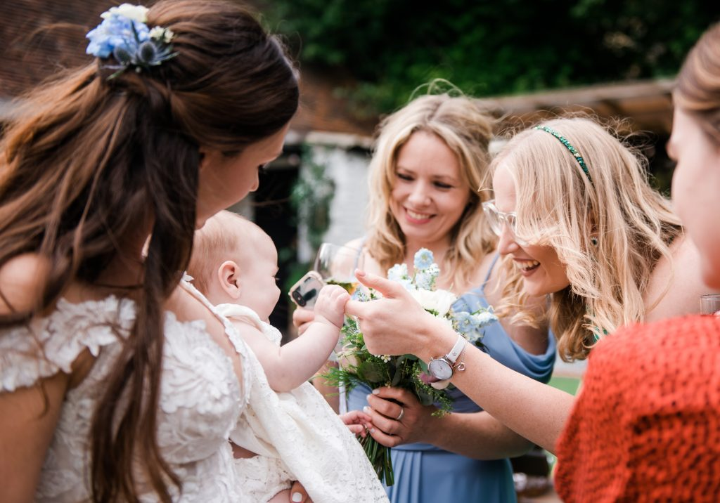 wedding guests hold the hand of baby