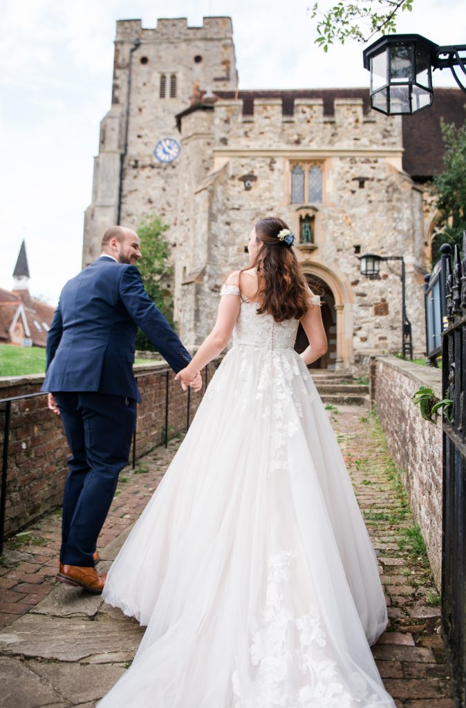 wedding couple walk hand in hand  up to the church