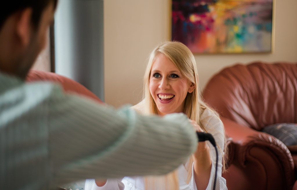 candid shot of bride smiling as she has her hair done