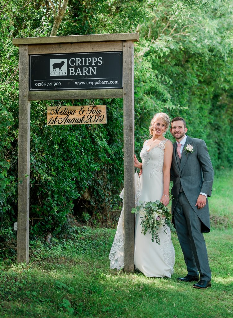 couple get a picture with the sign of their wedding venue