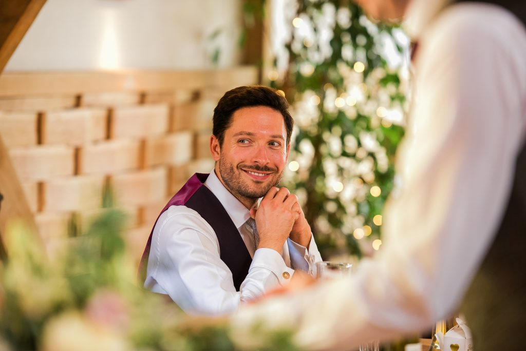 documentary style shot of wedding guest smiling
