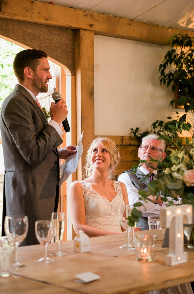 groom delivering his speech whilst his bride looks up at him smiling