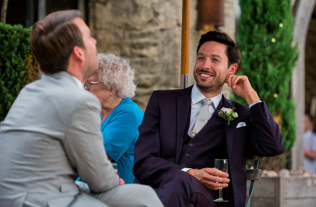 candid shot of wedding guests smiling to his partner