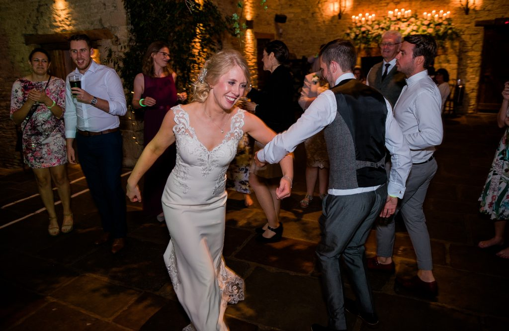 bride and groom linking arms on the dance floor